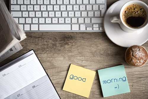 Digital tablet computer with sticky note paper and cup of coffee
